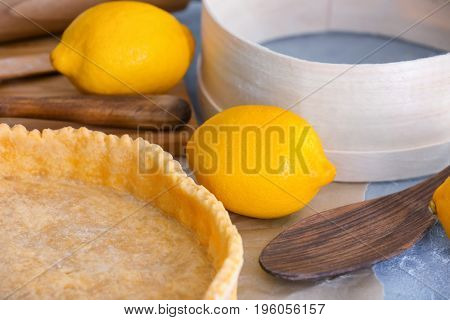 Empty pie crust and lemons on table, closeup
