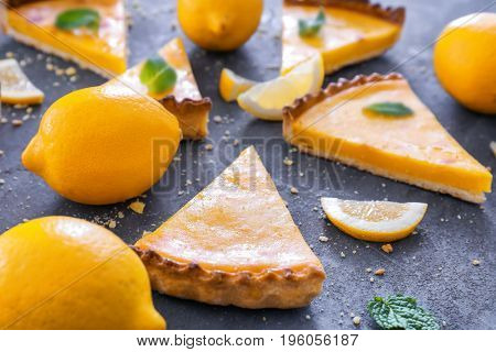 Composition with pieces of delicious lemon pie on textured background
