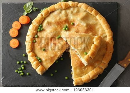 Composition with delicious turkey pot pie on gray table