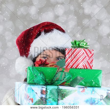 Closeup of a young woman peeking out from behind a stack of christmas presents she is carrying.
