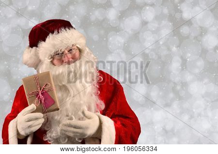 Closeup of Santa Claus holding a Christmas Present. Horizontal format with a light bokeh background.