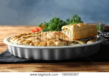 Baking dish with turkey pot pie on wooden table, closeup