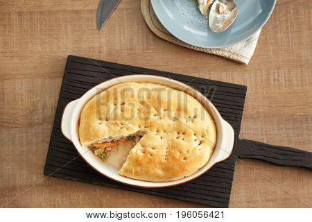 Baking dish with turkey pot pie on wooden table