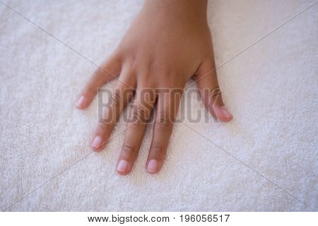 Overhead view of hand on white towel at hospital ward