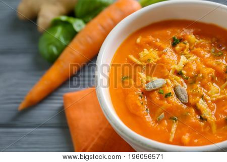 Delicious carrot soup on wooden table