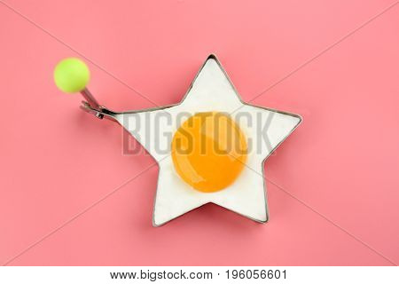 Fried sunny side up egg in star shaped mold on color background