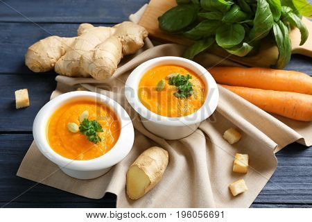 Composition with delicious carrot soup, basil leaves and fresh ginger on wooden table