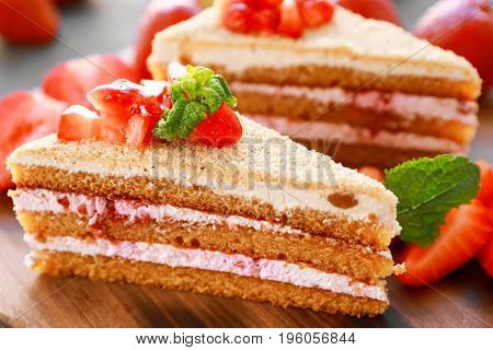 Two pieces of homemade cake with strawberries on wooden board