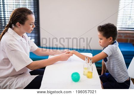 Side view of female therapist examining hand while boy sitting at table in hospital ward