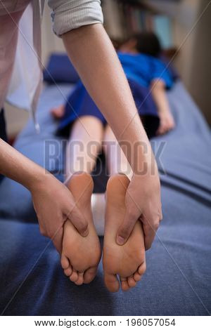 Boy lying on bed while receiving foot massage from young female therapist at hospital ward