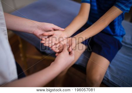 Midsection of female therapist examining hands with boy sitting on bed at hospital ward