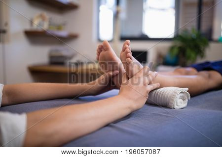 Low section of boy lying on bed while receiving foot massage from female therapist at hospital ward