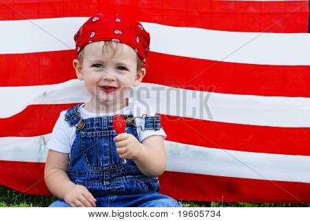 A cute young boy eating a sucker in front of an american flag