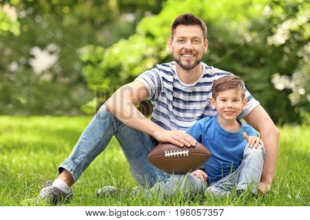 Dad and son with rugby ball in green park