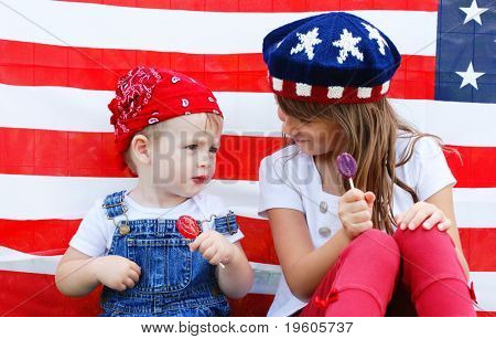 Two cute kids eating suckers by an american flag