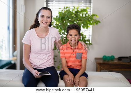 Portrait of smiling female therapist holding digital sitting with arm around boy on bed at hospital ward
