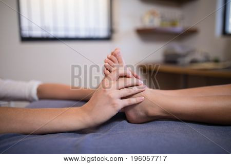 Low section of boy receiving foot massage from female therapist at hospital ward
