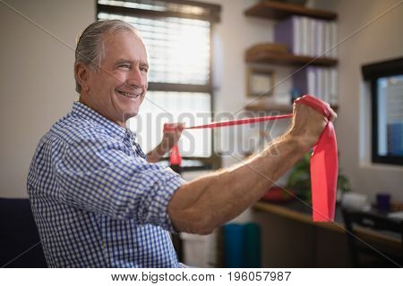 Smiling senior male patient pulling red resistance band at hospital