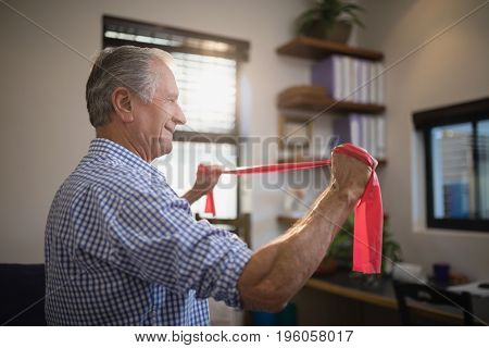 Side view of senior man pulling resistance band while standing in hospital ward