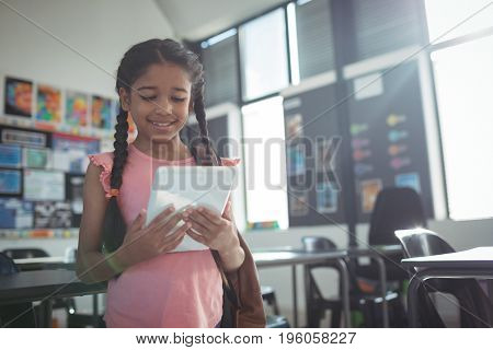 Smiling girl using digital tablet in classroom