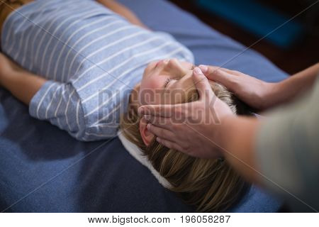 High angle view of female therapist giving head massage to boy lying on bed at hospital ward