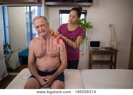 Female therapist applying elastic therapeutic tape on shoulder of frowning shirtless senior male patient at hospital ward