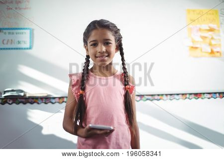 Portrait of girl holding mobile phone while standing against wall in school