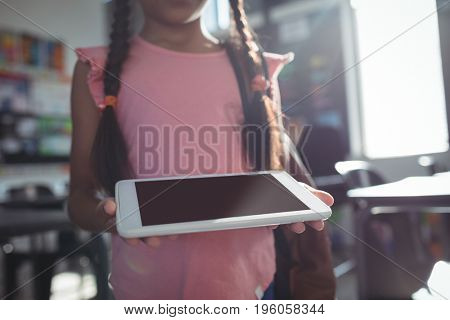Midsection of girl using digital tablet in classroom