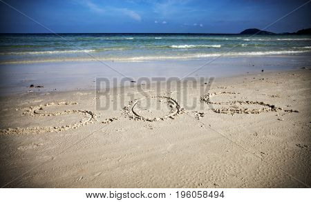 S.O.S written in the sand of an island with the ocean in the distance