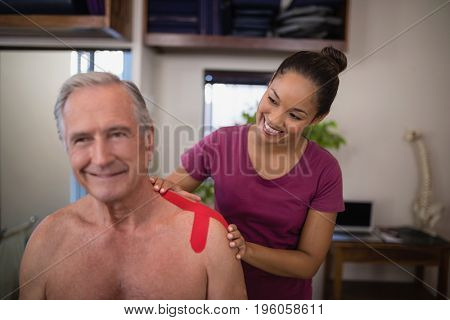 Smiling female therapist applying elastic therapeutic tape on shoulder of shirtless senior male patient at hospital ward