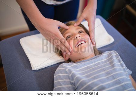 High angle view of smiling boy receiving massage from female therapist at hospital ward