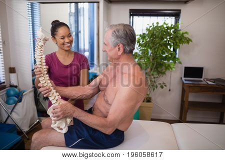 Smiling female therapist looking at shirtless male patient holding artificial spine at hospital ward