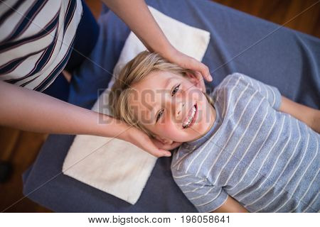 High angle portrait of smiling smiling boy receiving massage from female physiotherapist at hospital ward