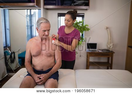 Female therapist applying elastic therapeutic tape on shoulder of shirtless senior male patient at hospital ward