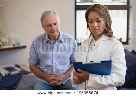 Senior male patient and female therapist looking at file in hospital ward