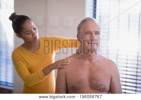 Female therapist giving neck massage to shirtless senior male patient at hospital ward