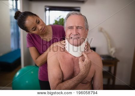 Female therapist looking at senior male patient grimacing with neck collar in hospital ward