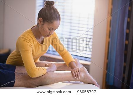 Young female therapist massaging calf of male patient at hospital ward
