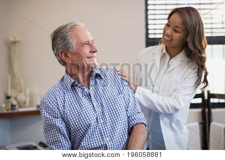 Smiling female therapist looking at male patient against window at hospital ward