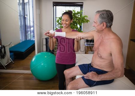 Smiling female therapist holding hand of senior male patient at hospital ward