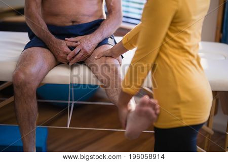 Midsection of female therapist massaging high of senior male patient at hospital ward