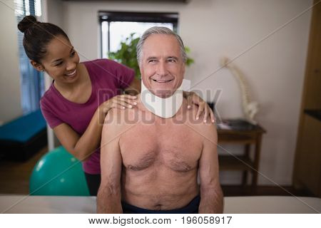 Smiling female therapist looking at senior male patient with neck collar in hospital ward