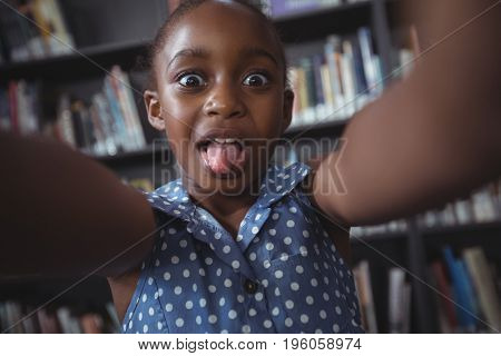 Portrait of happy girl making face against bookshelf in library