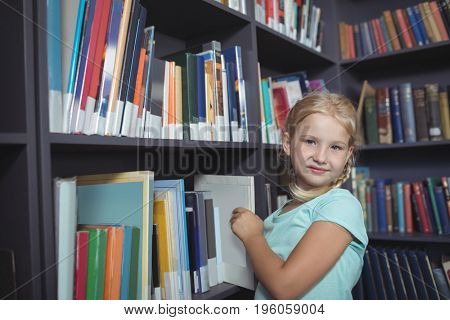Portrait of girl choosing book from shelf at library