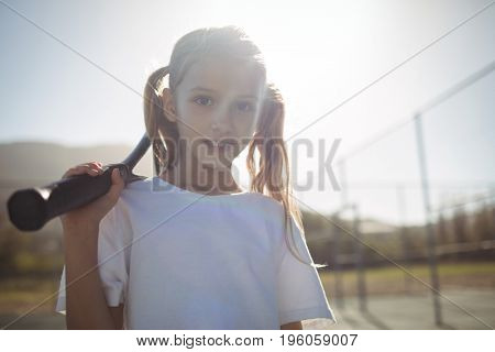 Portrait of girl with tennis racket at court on sunny day