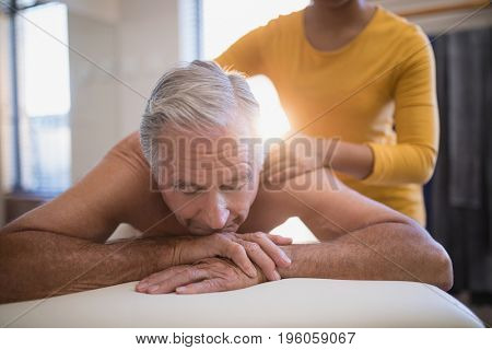 Shirtless male patient lying on bed receiving neck massage from young female therapist at hospital ward