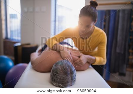 Shirtless male patient lying on bed receiving neck massage from female therapist at hospital ward