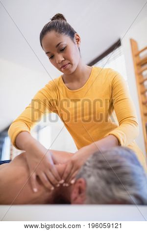 Low angle view of female therapist giving neck massage to male patient at hospital ward