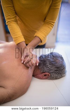 High angle view of female therapist giving neck massage to shirtless male patient at hospital ward