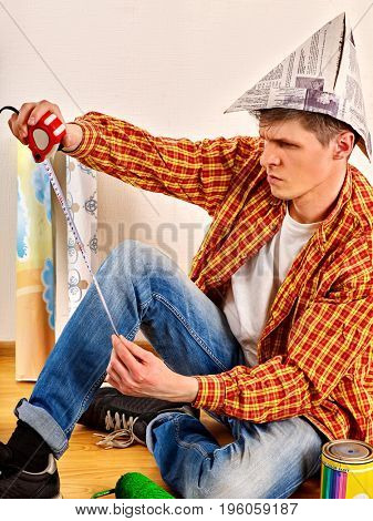 Repair home man holding paint bank. Tired and frustrated mad male in newspaper cap renovation apartment. Paint bank and paint brush in hand. He measures the room with a tape measure.